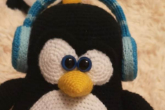 Tux - the symbol of Linux listening music